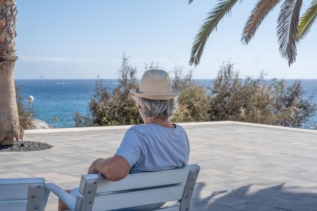 Вид сзади седого пожилого мужчины на открытом воздухе у моря, сидящего в тени дерева