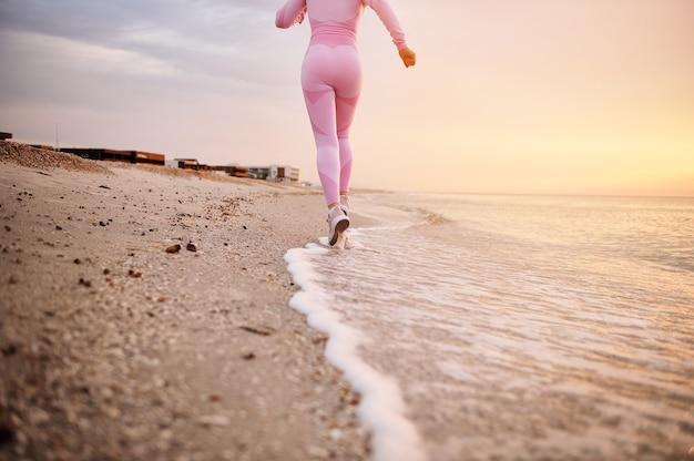Вид сзади спортсменки, бегущей по пляжу у кромки воды
