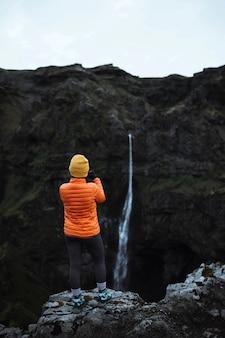 滝の景色をキャプチャする女性の背面図