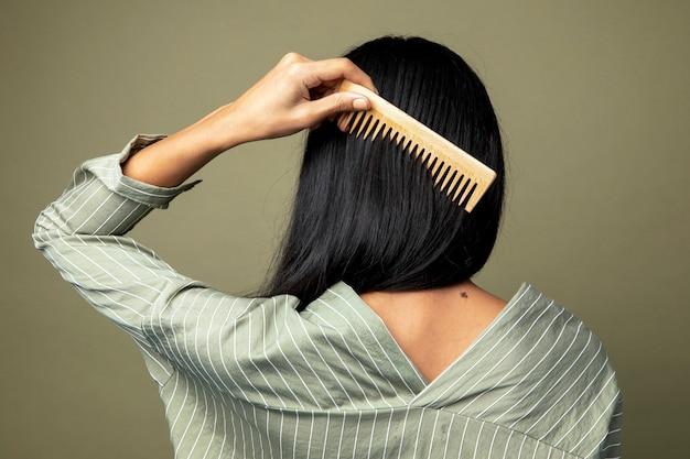 彼女の髪をとかす女性の背面図