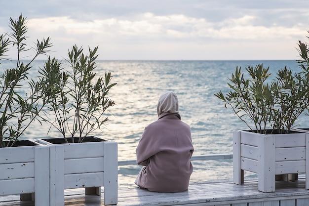 寒い季節に海を見ているコートを着た女性の背面図。