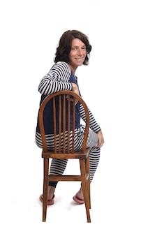 Вид сзади женщины в пижаме, сидящей на стуле на белом backgraund, смотрящей в камеру