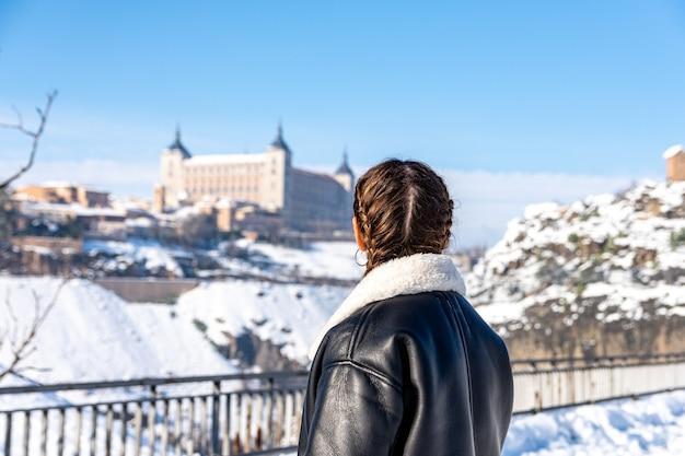 Вид сзади женщины, смотрящей на снежный город толедо. снежный пейзаж.