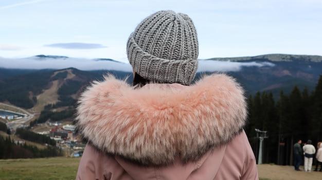森と曇り空の秋の風景を眺める山々を背景に、毛皮と灰色のニット帽子を着たピンクのジャケットを着た女性の山岳観光客の背面図。