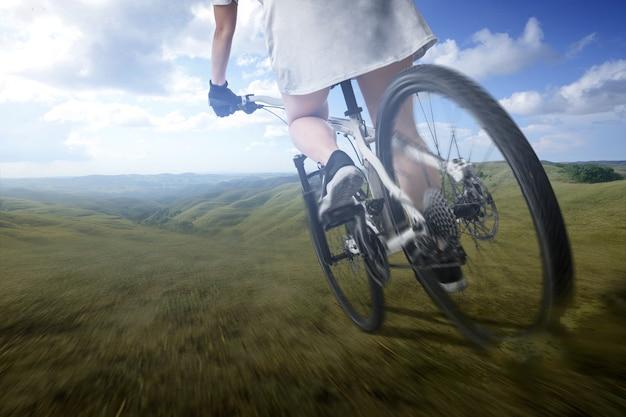 Вид сзади женщины, едущей на велосипеде на луговом поле