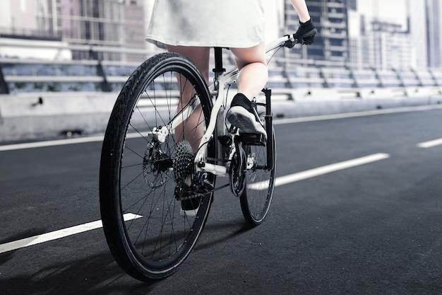Вид сзади женщины, едущей на велосипеде по улице