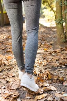 Вид сзади ноги у женщины ходьбе на сухих листьев