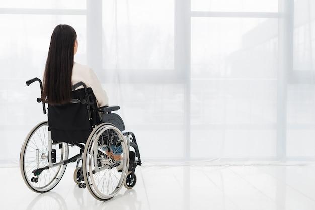 Вид сзади женщины, сидя на инвалидной коляске, глядя на окна