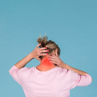 Rear view of a woman suffering from neck pain in front of blue backdrop