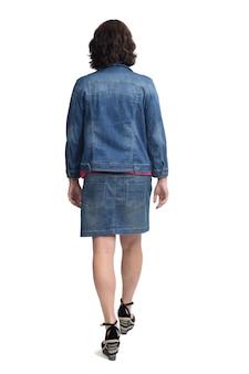 Вид сзади женщины, идущей в джинсовой юбке и куртке на белом фоне