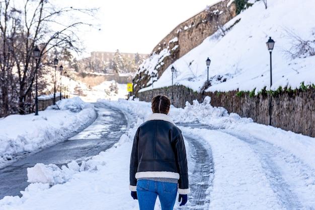 눈 덮인 도시 도로에 걷는 여자의 후면 볼 수 있습니다.