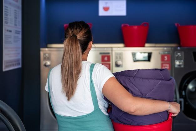 コインランドリーに洗濯かごを持った女性の背面図。