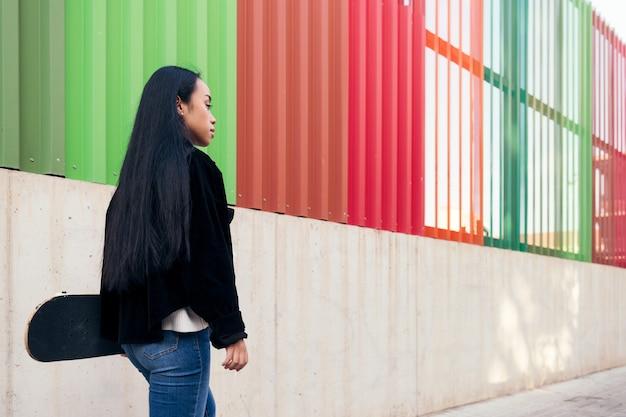 스케이트보드를 손에 들고 거리를 걷고 있는 젊은 아시아 여성의 뒷모습
