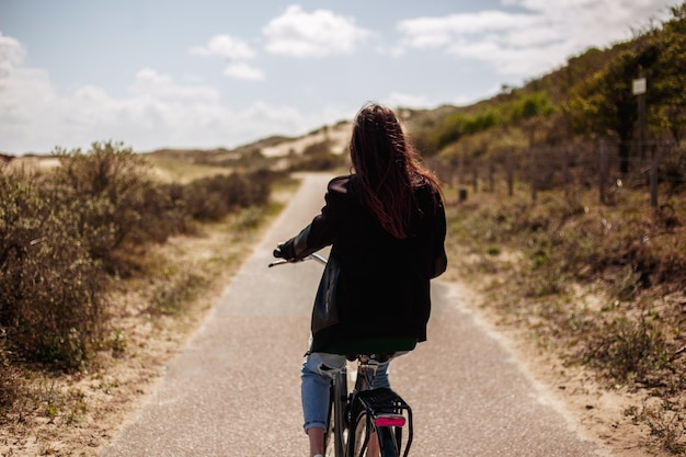 Вид сзади молодой красивой девушки идет один на велосипеде по дороге в солнечный день.
