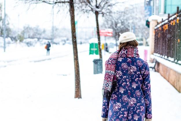 街の雪道を歩いている冬服を着た若いブロンドの女性の背面図。