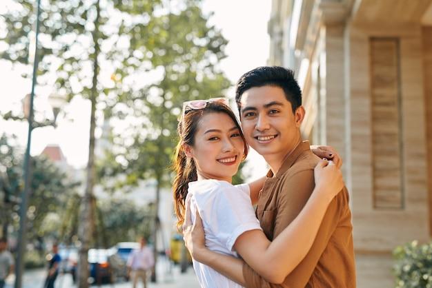 Вид сзади молодой пары, обнимающейся в городе назначения, стоя в торговом районе рядом с обувным магазином класса люкс, на открытом воздухе