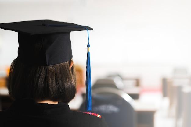 Вид сзади молодой счастливой выпускницы университета из юго-восточной азии в выпускном платье и выпускной шапке в кампусе колледжа