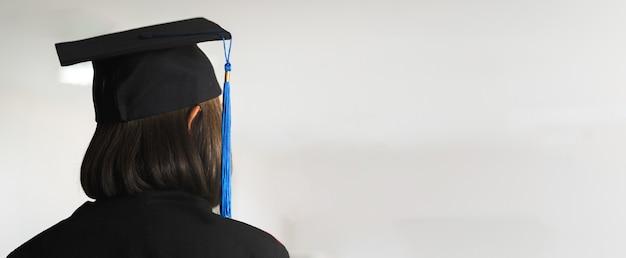 大学のキャンパスで卒業ガウンと卒業帽で若い幸せな東南アジアの女性大学卒業生の背面図