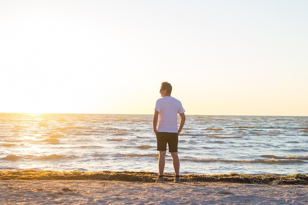 흰 셔츠와 일출 빈 해변에 서있는 갈색 반바지에 젊은 남자의 후면 볼 수 있습니다.