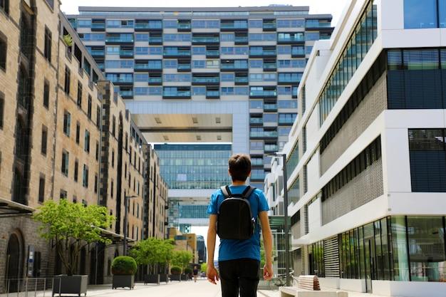バックパックを持った若い男の背面図が大都会に到着し、展望と機会を持つモダンな建物を探しているところ