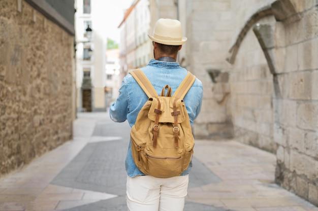 旧市街の通りを歩いているバックパックと若い男の背面図