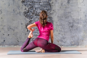 Rear view of a young woman doing yoga pose in front of grey wall
