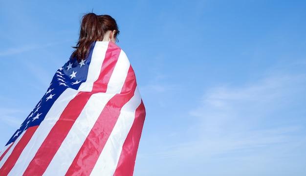 青いskに対して彼女の肩にアメリカの国旗を持っている若い女性の背面図