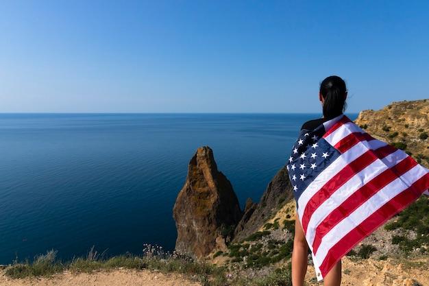 Вид сзади молодой женщины, держащей американский флаг, развевающийся на береговой линии на фоне яркого моря