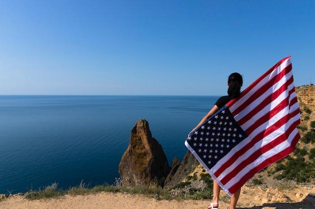 Вид сзади молодой женщины, держащей американский флаг, размахивая на береговой линии против солнечного яркого моря.