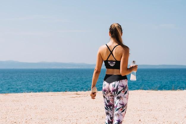海を見下ろす水瓶を持っている若い女性のリアビュー