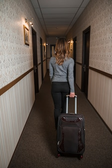Rear view of a young woman pulling her suitcase in the hotel corridor