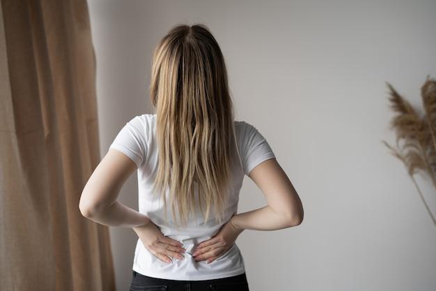 部屋に立って背中の痛みに苦しんでいる若い女性の背面図。テキスト用の空き容量。