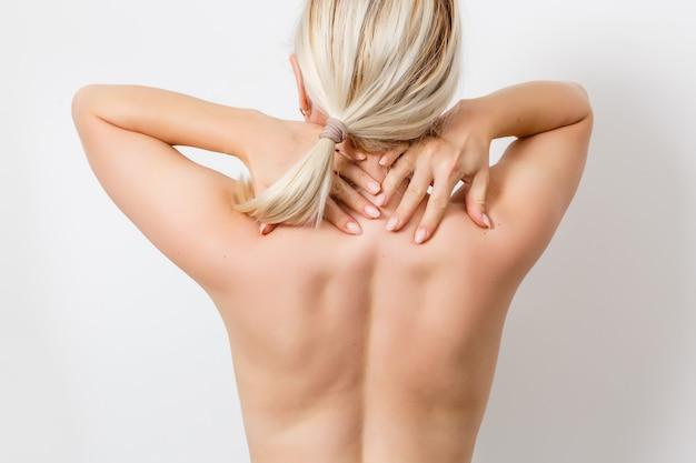 Вид сзади молодой женщины, касающейся ее спины