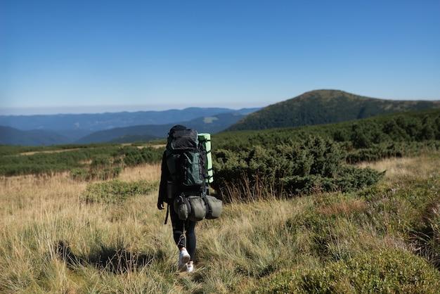 大きなバックパックを持った若い女性観光客の背面図が山の平原を歩いています