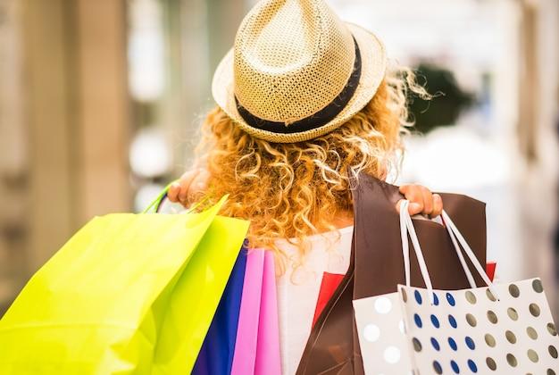 ショッピングモールに歩いて金髪と巻き毛の若い女性の背面図