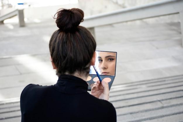 Вид сзади молодой женщины с хвостиком, сидящей на ступеньках на открытом воздухе во время использования кисти для макияжа