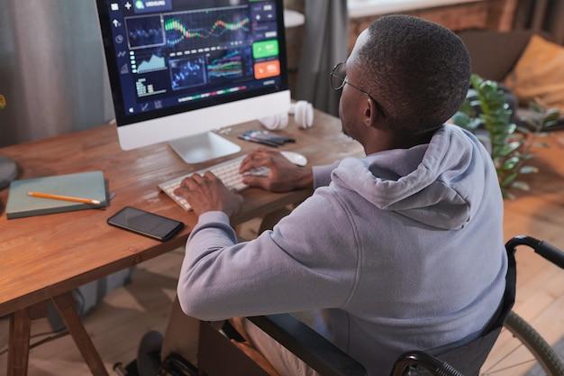 自宅で作業中に新しいソフトウェアを開発するコンピューターで入力するアフリカの障害者の男性の背面図