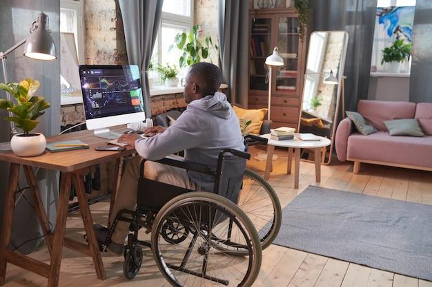 コンピューターのモニターの前のテーブルで車椅子に座って、自宅でソフトウェアを操作しているアフリカ人男性の背面図