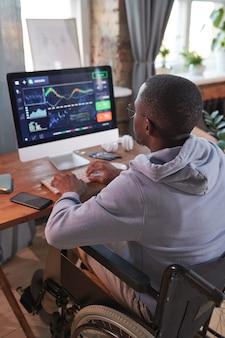 コンピューターのキーボードで入力し、自宅でコンピュータープログラムで作業している車椅子に座っているアフリカ人男性の背面図