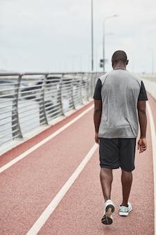 トレーニング後のスタジアムに沿って歩くスポーツウェアのアフリカのスポーツマンの背面図