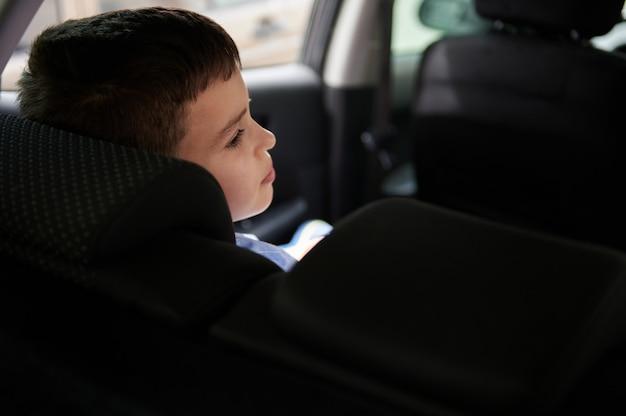 車の後部座席の愛らしい男子生徒の背面図