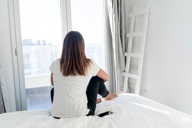 Вид сзади взрослой расслабляющей женщины, сидя на кровати