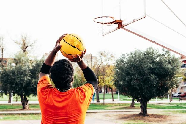 바구니에 공을 쏠 준비가 아프리카 계 미국인 흑인 소년의 후면보기.