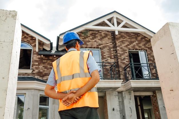 建設現場でベストとヘルメットをかぶったアメリカのインド国民労働者の背面図は、家の建物を見て検査します