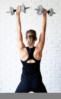 Вид сзади спортивной женщины в черной спортивной одежде, демонстрирующей мышцы спины и рук