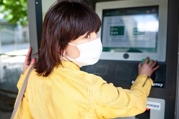 保護マスクを着用した身元不明の女性の背面図は、ぼやけた情報ボードに指を向けています