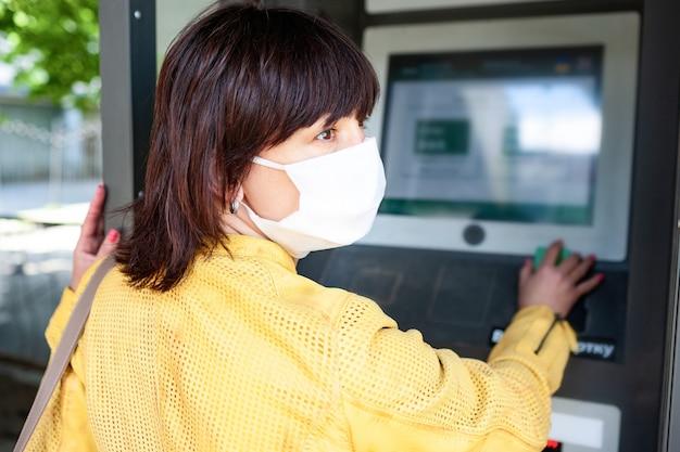 Вид сзади неопознанной женщины в защитной маске указывает пальцем на размытое информационное табло