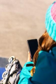 도시 스케이트장에서 그녀의 휴대 전화를 사용하여 인식 할 수없는 여성 스케이팅의 후면보기. 도시 스케이트 개념과 기술.