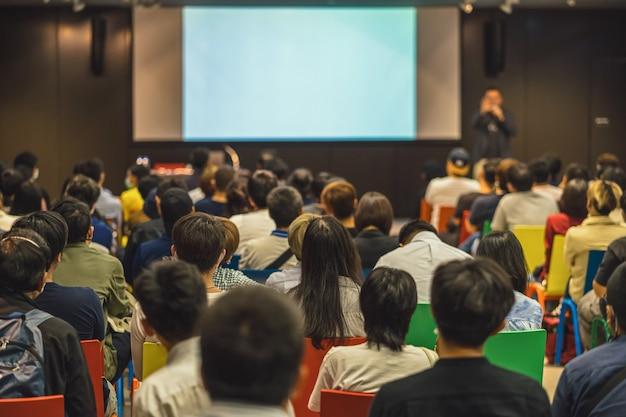 セミナーのステージで話しているスピーカーに参加し、聞いているアジアの聴衆の背面図