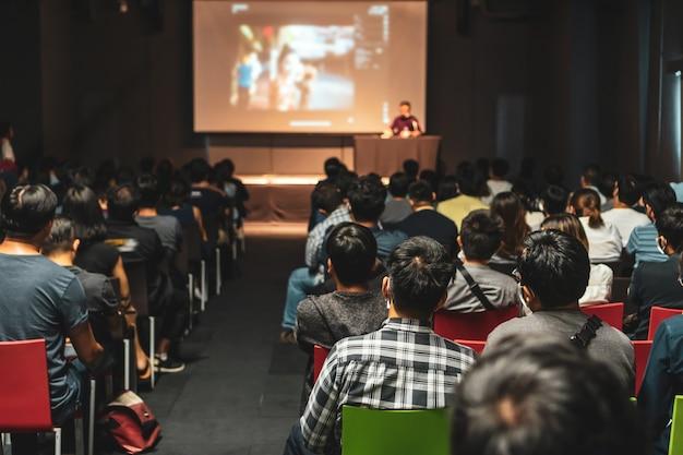 세미나의 무대에서 연설하는 아시아 청중이 합류하고 경청하는 모습